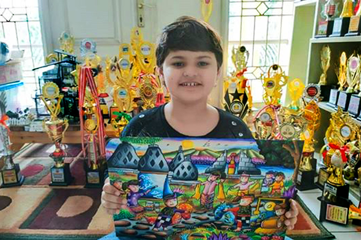 A boy poses with his drawing