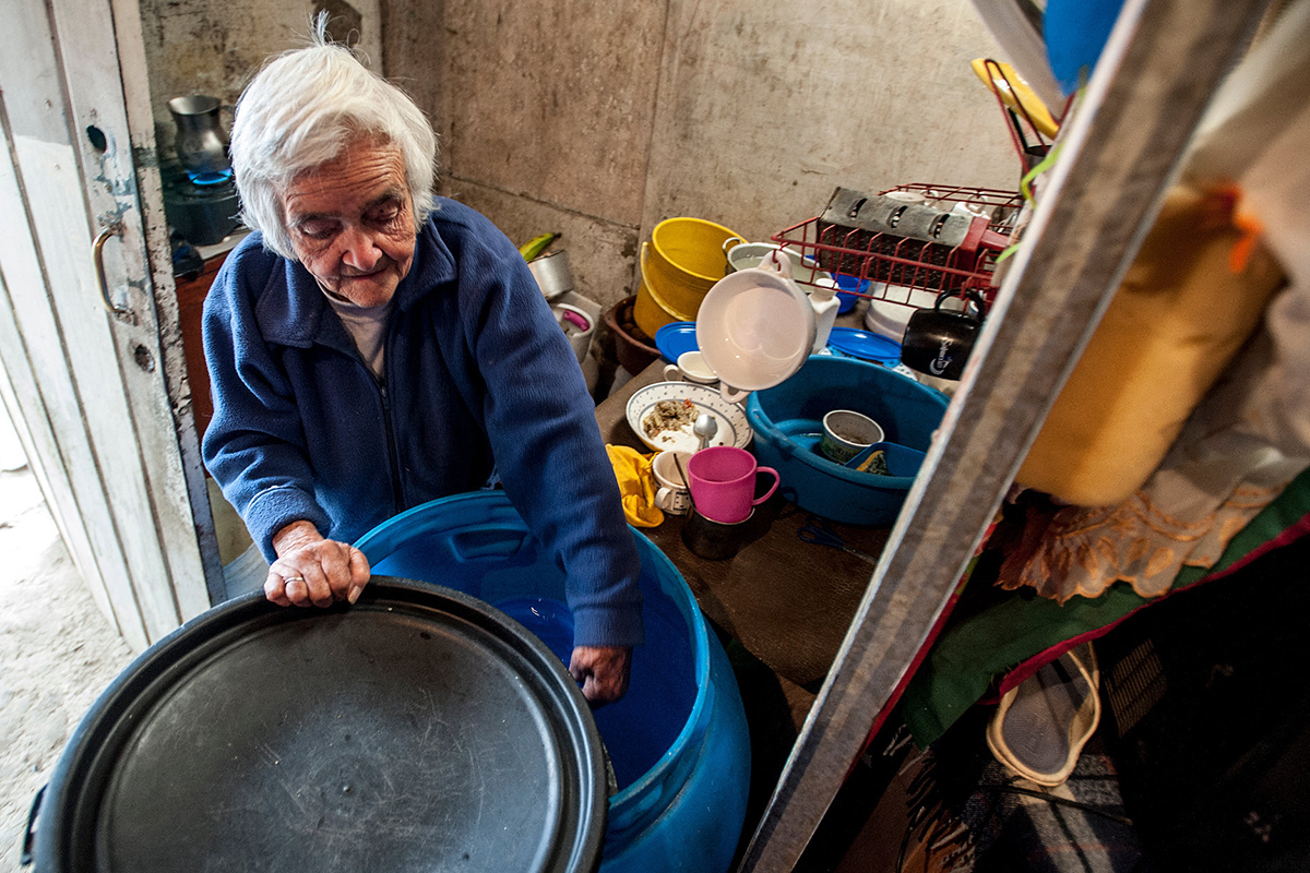 An older woman working in a kitchen