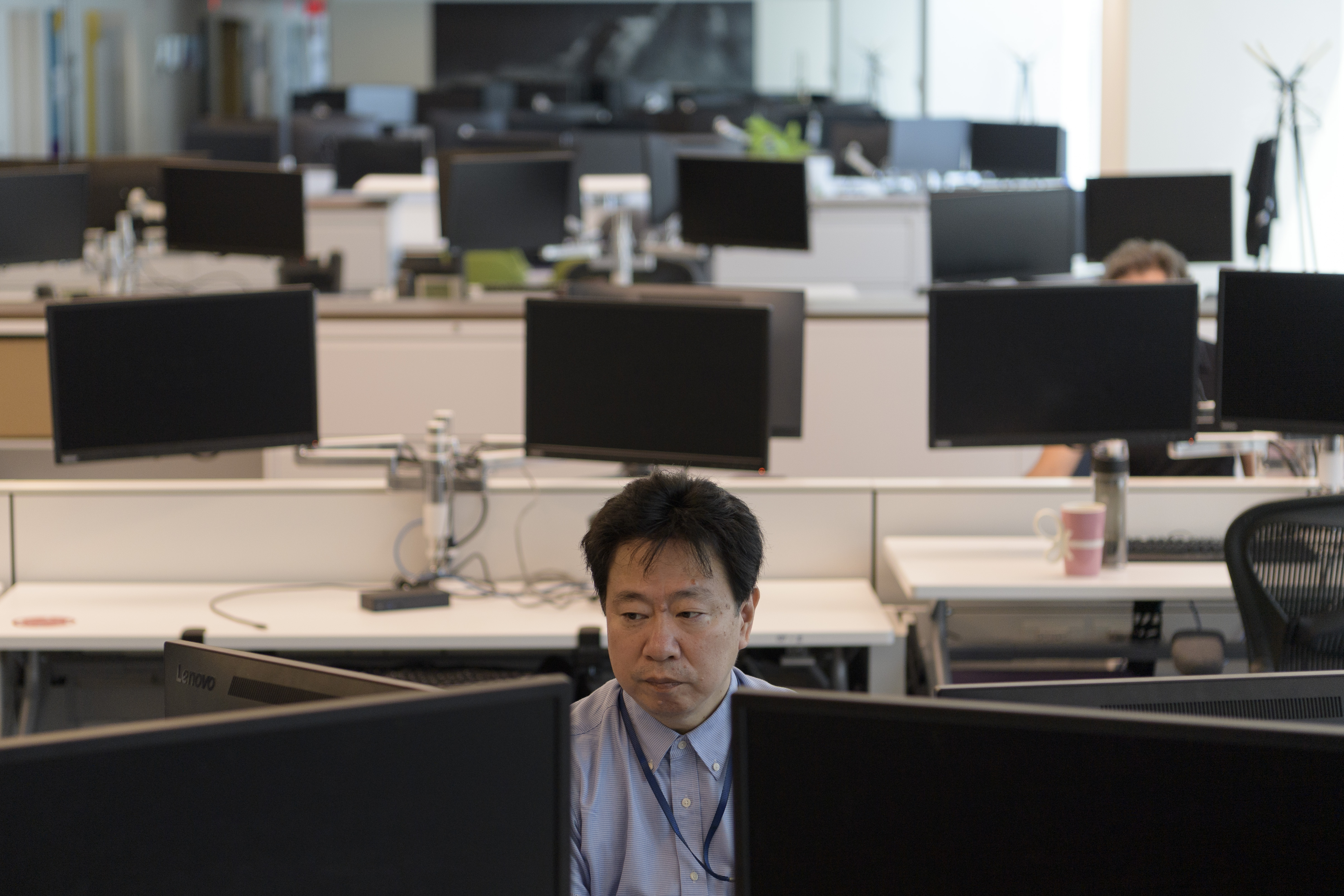 Man sitting at a desk in an open desk space.