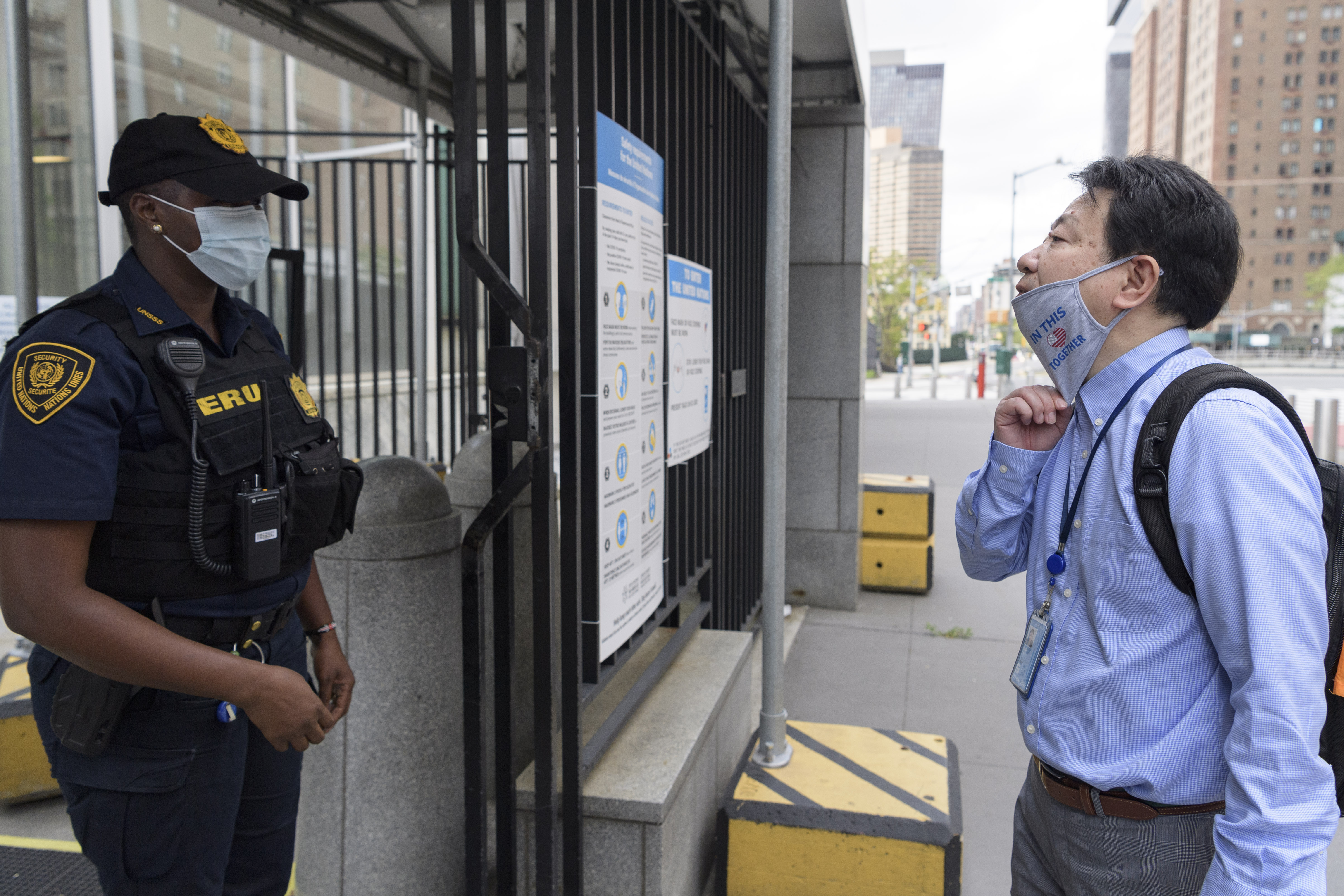 Man lowers his facemask in front of a Security Officer