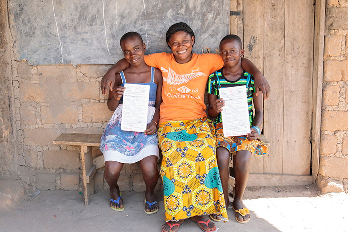 two girls sit on each side of their mother as they hold up their birth certificates