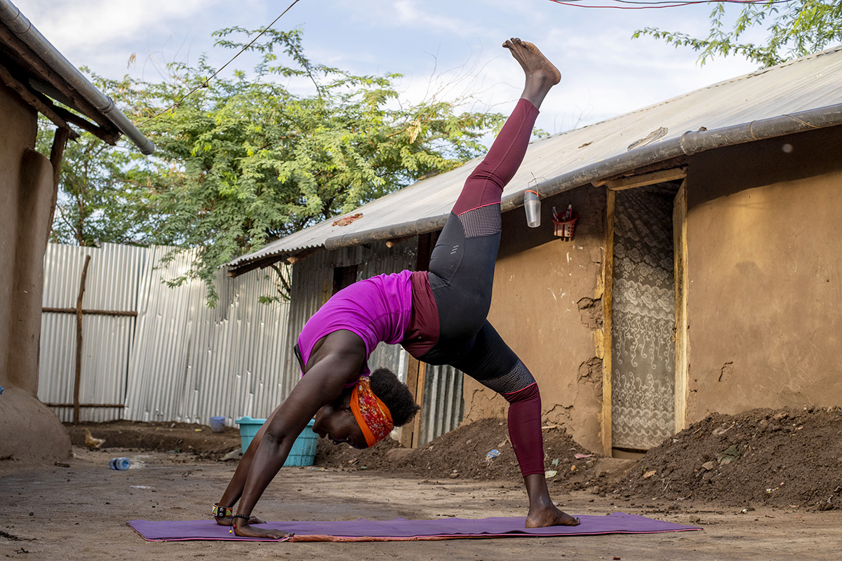 A woman does a backbend yoga pose outdoors.