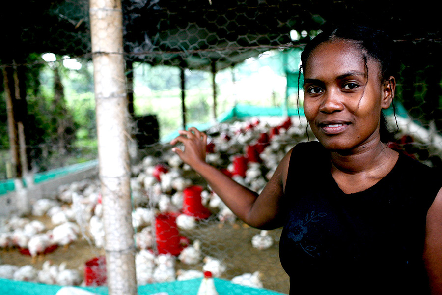 Portrait of a woman in front of a chicken farm.