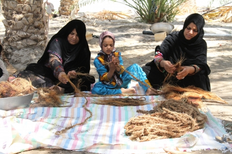 Women make rope while sitting on a blanket on the sand