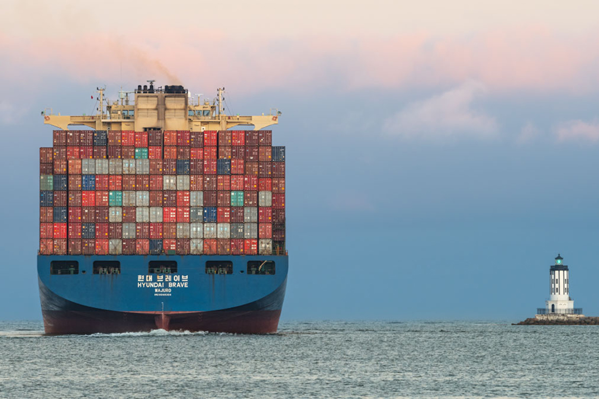 A big ship loaded with shipping containers passing by a lighthouse.