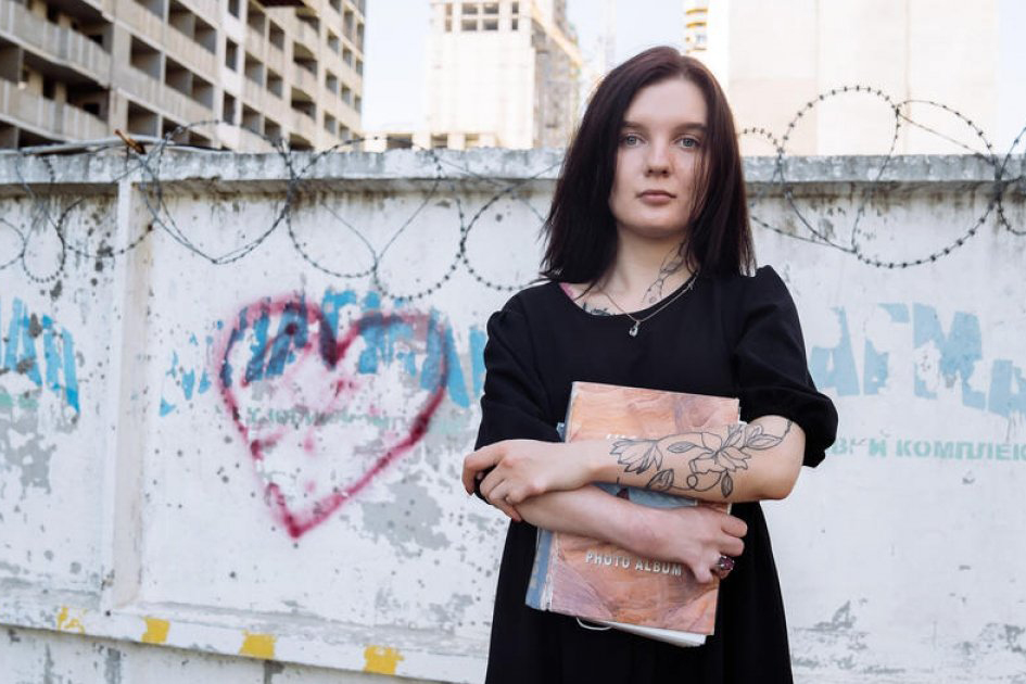 young woman in front of wall with barbed wire and grafitti