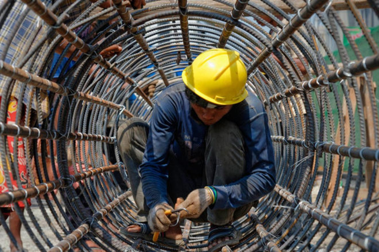 A construction worker builds a cylindrical metal structure in Yangon, Myanmar.