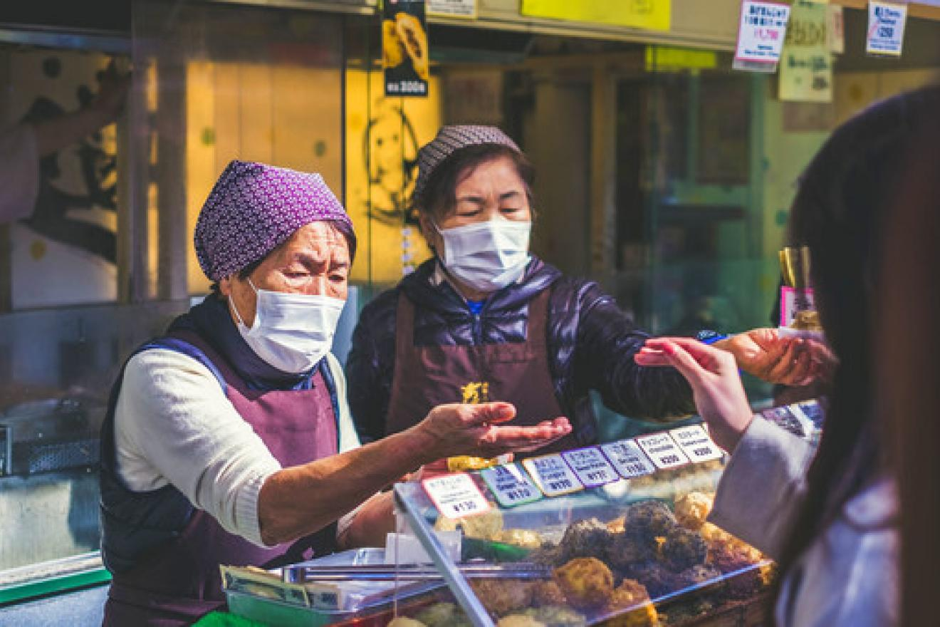 Vendors wear face masks at a food market in Japan.