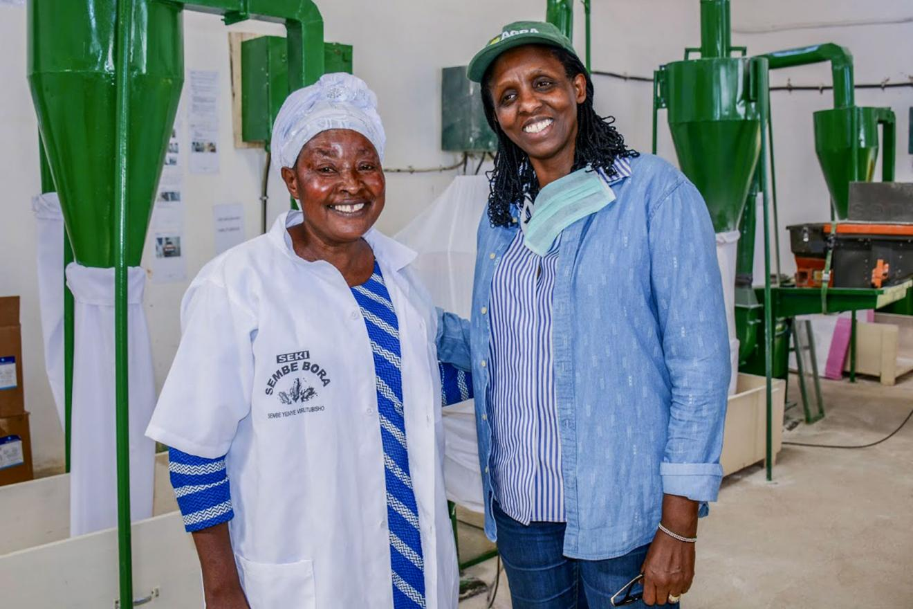 Dr. Kalibata poses for a photo with a female worker in an milling plant.