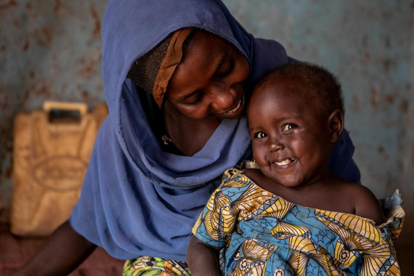 A woman is looking at her smiling child.