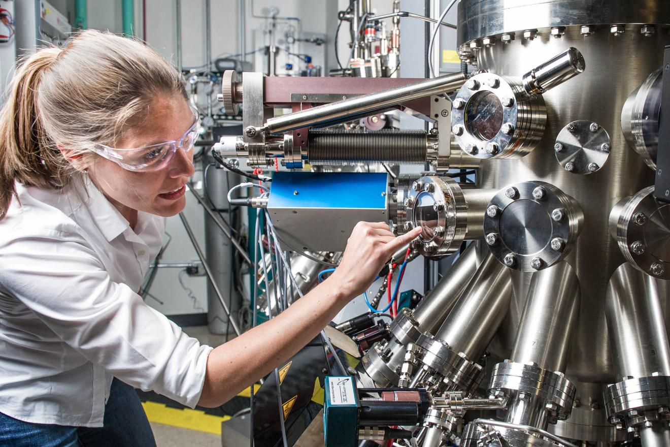 NREL scientist uses a Compound Semiconductor Molecular Beam Epitaxy System to grow semiconductor samples in the Semiconductor Growth lab at the Solar Energy Research Facility at NREL.