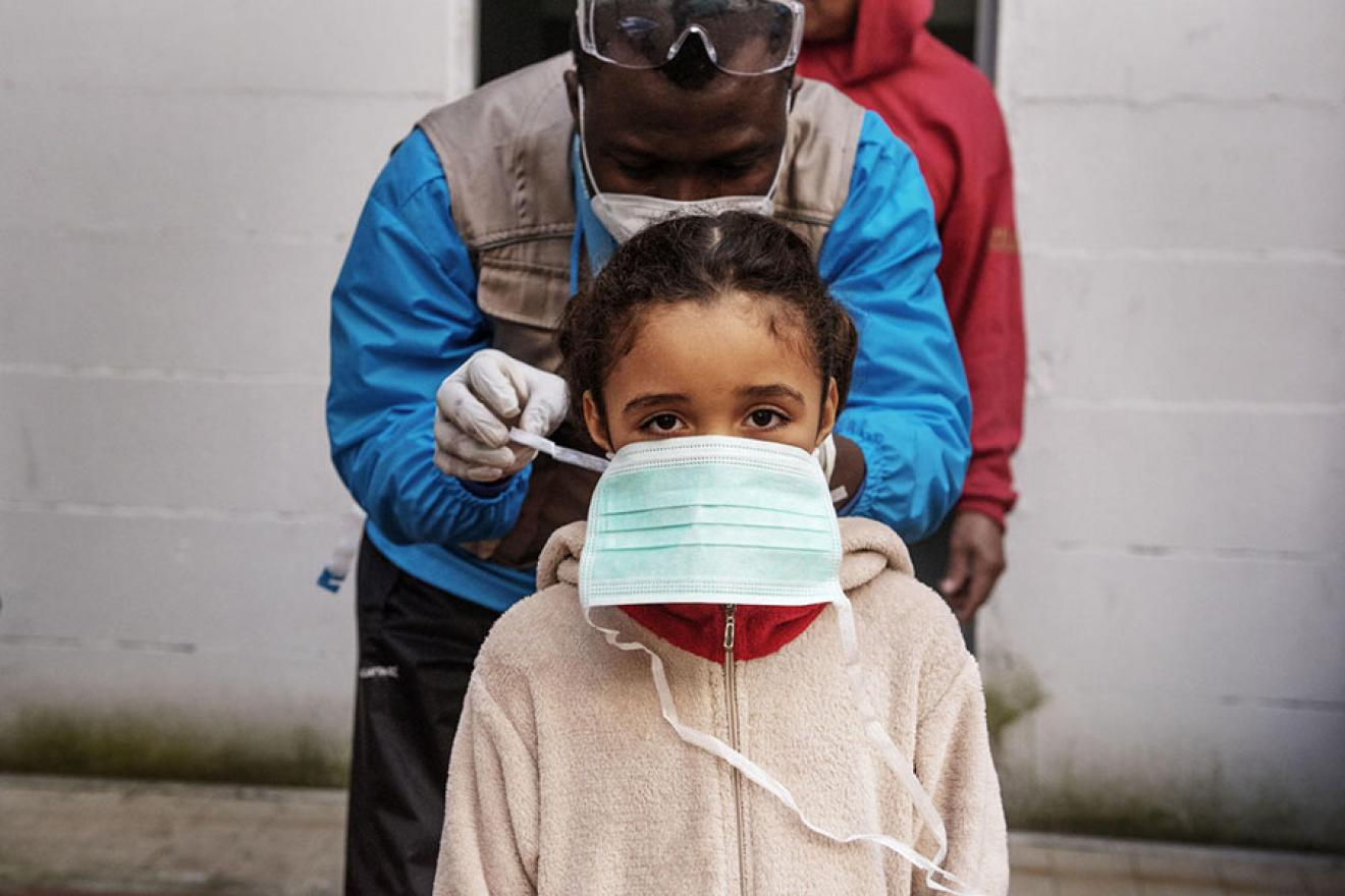 A health worker checking tying her facemask.