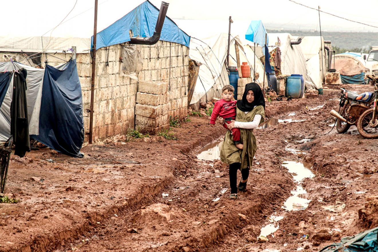 A girl carries a younger boy while walking through the mud.