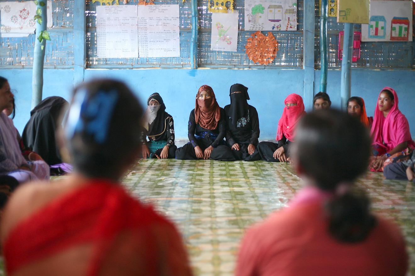 A group of women sitting in a circle on the floor.