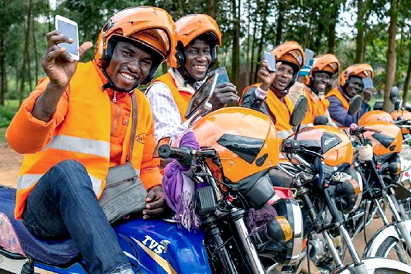 Motorcycle drivers line up and hold up their mobile phones.