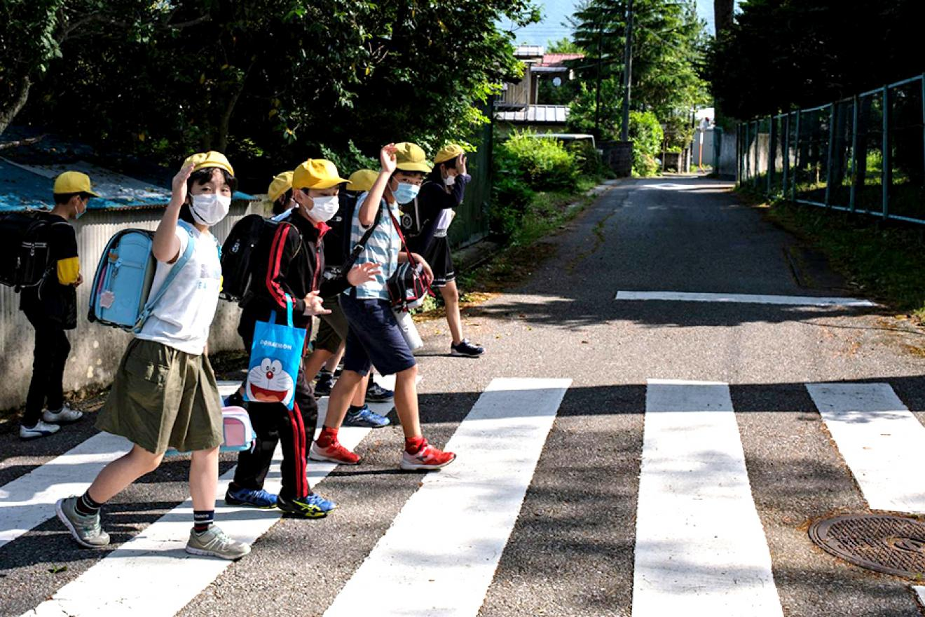 Group of children wearing facemasks wave as they walk through a crosswalk.