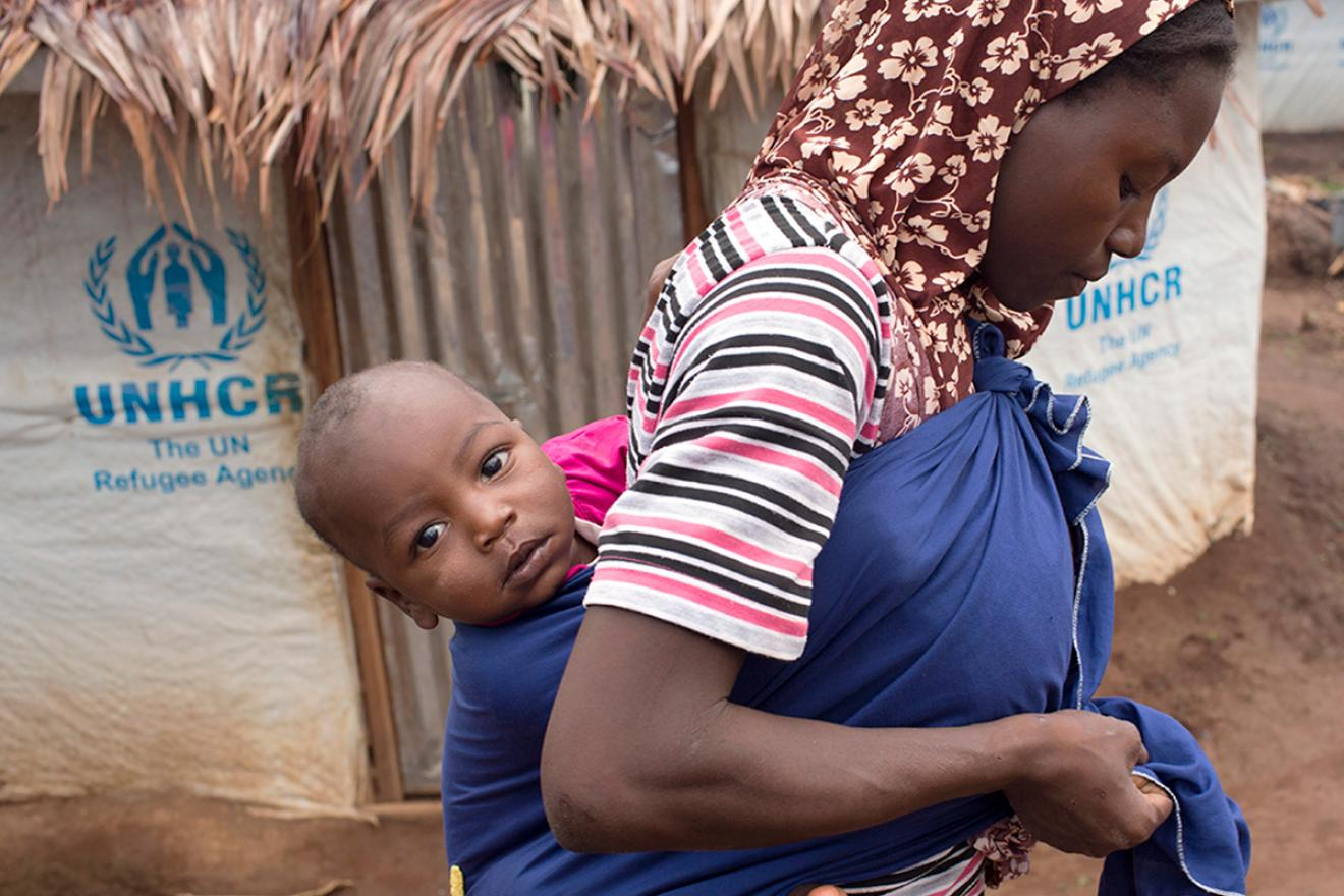 a woman carrying a baby on her back