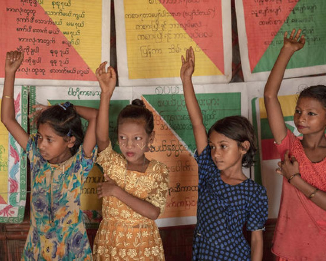 Children raise their hands to answer a question in class at a UNICEF learning space in Cox's Bazar, Bangladesh. (8 July 2019).