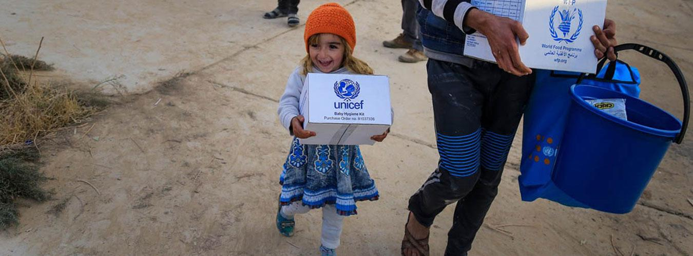 A young girl and her parent holding boxes of aid from UNICEF and WFP