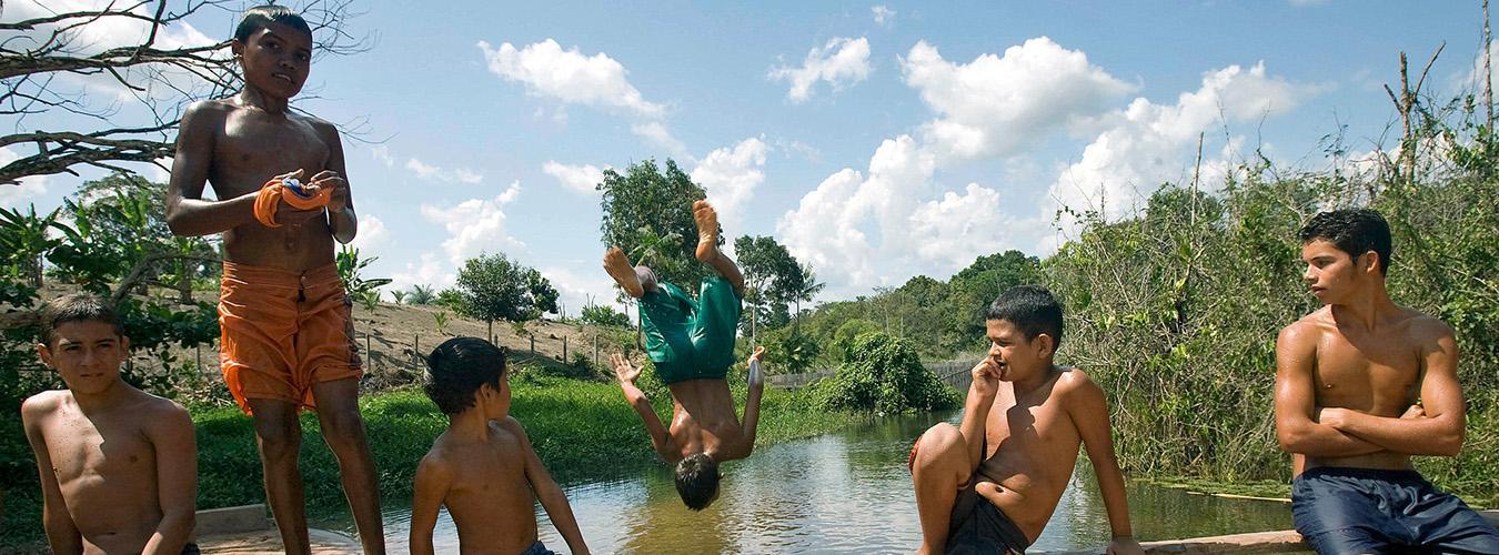 A group of adolescents watch peer jump in river