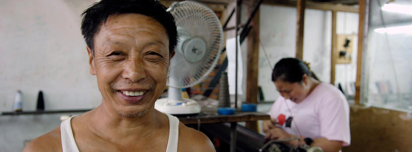 A close-up of a smiling man with a smiling woman sewing in the background.