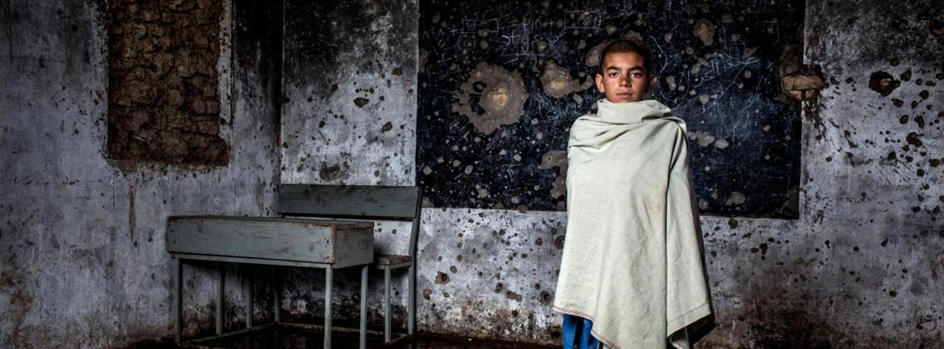 student at bombed out classroom in Afghanistan