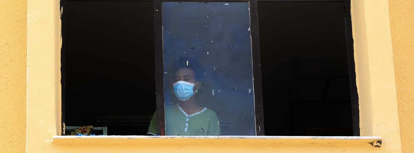 young woman with face mask at window
