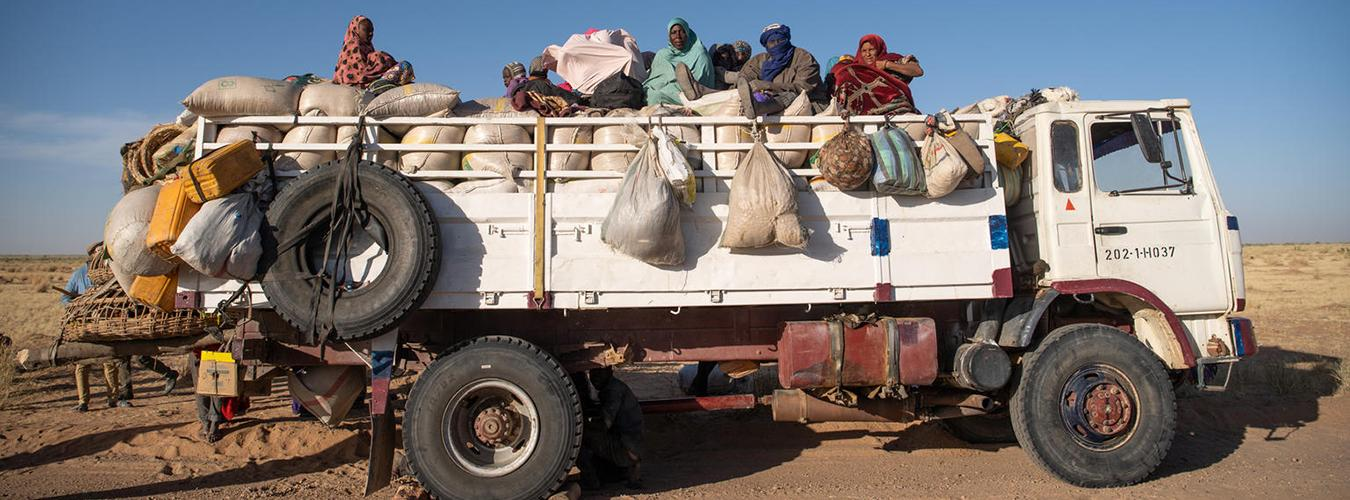 People travel inside a truck bed.