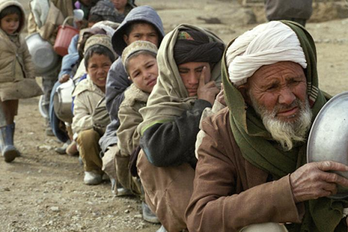 A group of internally displaced persons in Afghanistan seated in a row.