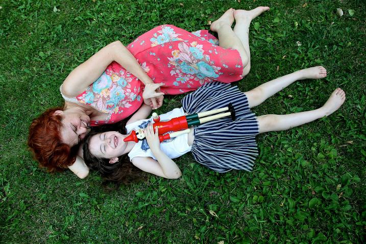 Mariam, 7, lies in the grass with her mother at Boghossian Gardens, Yerevan, Armenia.