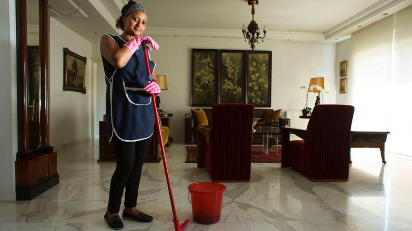 Woman stands with a mop and bucket in a living room.