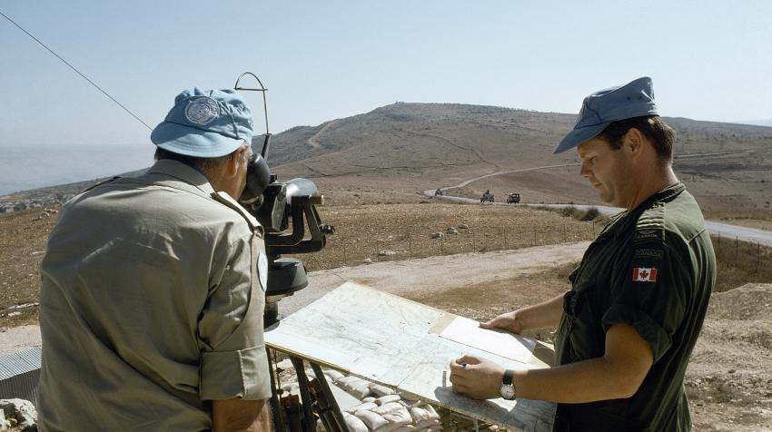 Two male observers observe machine-gun fire by Israel forces,