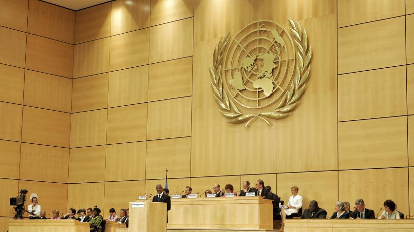 Frontal view of the Assembly Hall with UN emblem on bright colored wooden wall and a set of podiums and tables in the front.