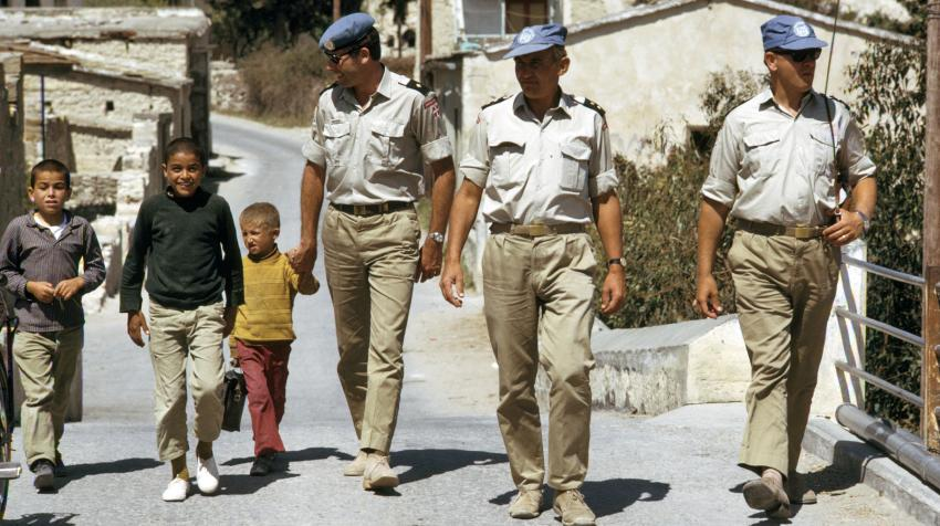Three male soldiers are walking with children while patrolling the streets.