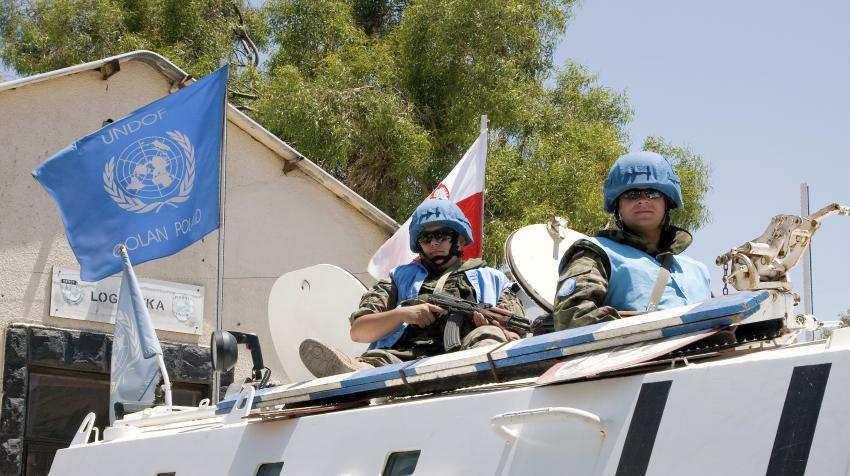Two Polish peacekeepers are riding on a white patrol vehicle with the Polish national flag and the UN flag.