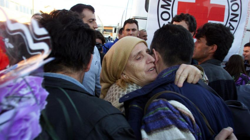 A woman hugging a man, who reunited with his family.
