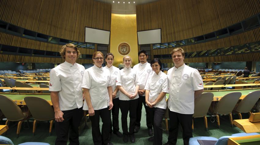 Master chef crew, all dressed in white chef uniforms, are standing in the General Assembly Hall.