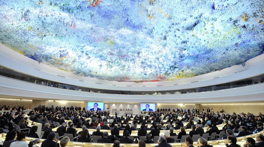 Eye-level view of a large circular conference room with a colorful ceiling containing dozens of seated individuals