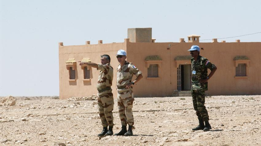 Three peacekeeper are on the road standing in front of a building in Western Sahara.