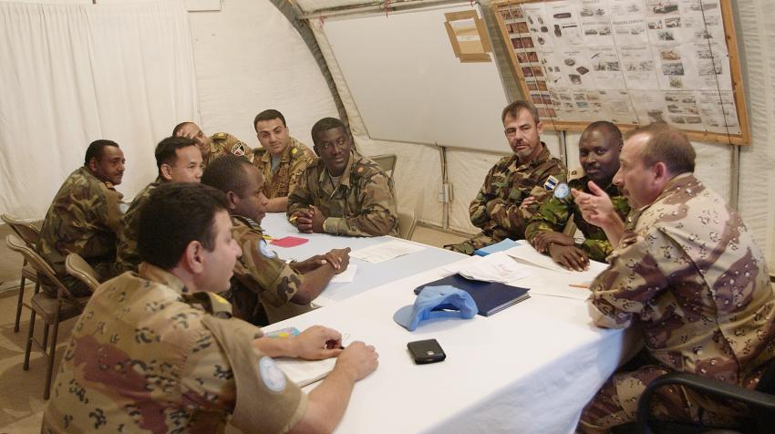 Peacekeeper are seated around a table at their office, participating in a briefing.