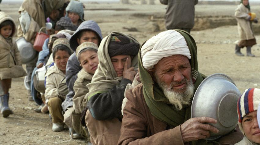 Afghans, from man to child, wait in line outside the kitchen for the wet feeding project funded by the World Food Programme.