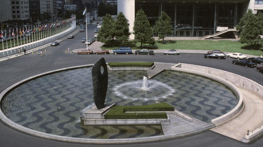 Overview of a circular pool with a fountain in the center, formed of alternating bands of crushed white marble and black pebbles, and an abstract sculpture at the edge of the pool.