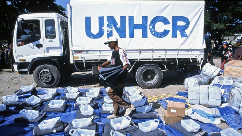 A UNHCR worker is preparing repatriation kits, including plastic sheeting, a blanket, a gerrycan, and soap, in front of a truck with the UNHCR logo on it.