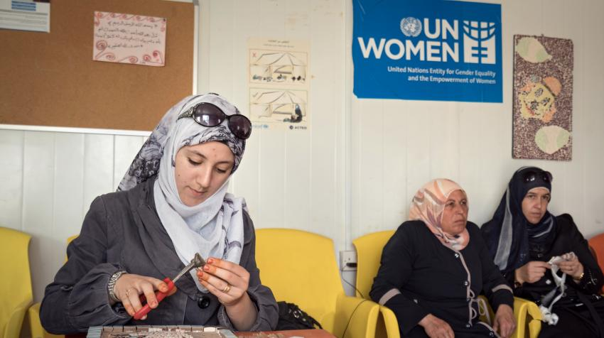Three women participating in a mosaic workshop led by UN Women.