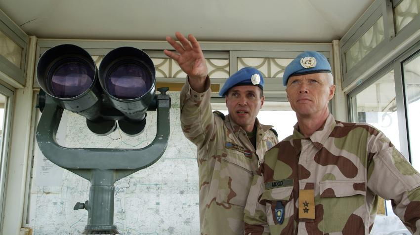Two male soldiers from the peacekeeping mission are standing next to binoculars at an observation post.