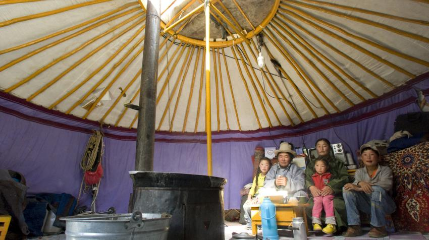 A Mongolian family is inside their ger, a traditional Mongolian tent, outfitted with a solar panel.