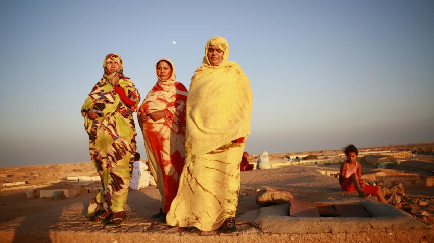 Three women are walking at sunset near a refugee camp in the Western Sahara area.