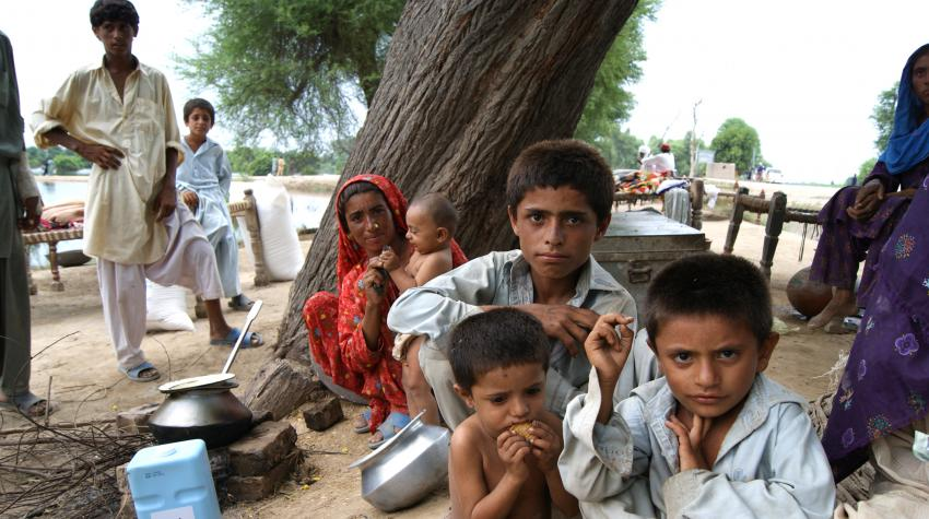 A Pakistani woman and children sit down on the ground with rations from the UN World Food Programme.