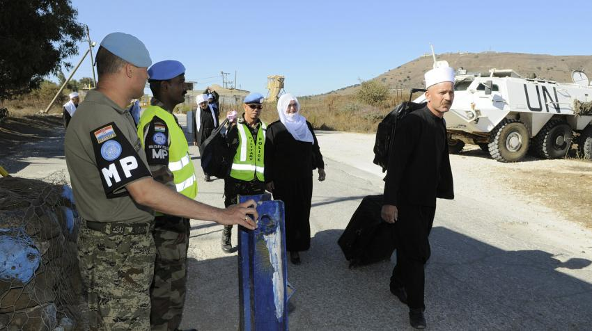 Several Druze pilgrims dressed in black body garment and white head garment are walking past a military checkpoint in Syria guarded by peacekeepers.