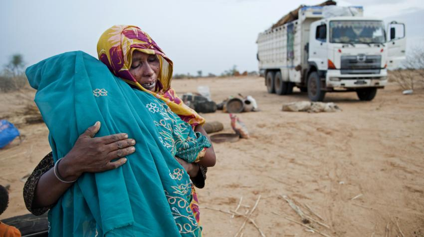 Two women are hugging each other emotionally as they return to their hom village in Sudan after living seven years in an Internally Displaced Persons camp.